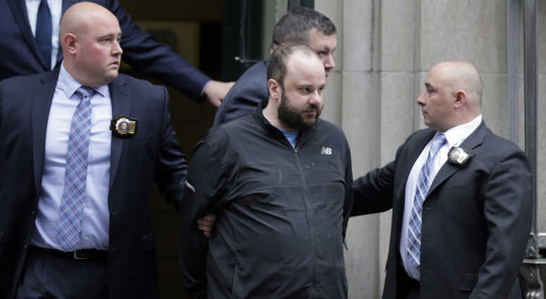 Marc Lamparello, 37, center, is escorted out of a police precinct in New York, Thursday, April 18, 2019.