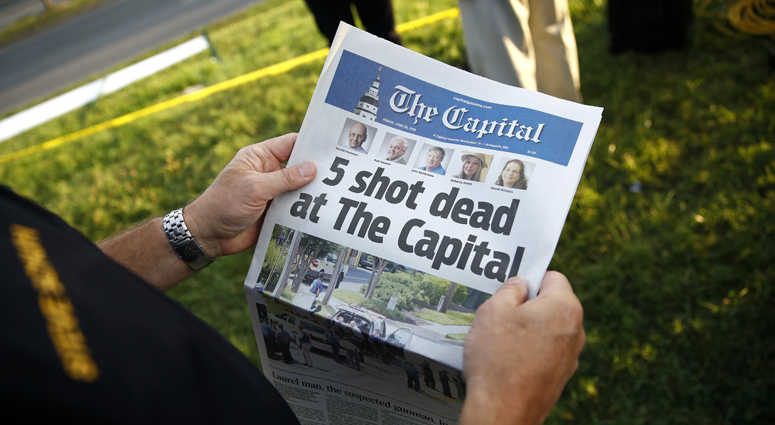 Steve Schuh, county executive of Anne Arundel County, holds a copy of The Capital Gazette near the scene of a shooting at the newspaper's office, Friday, June 29, 2018, in Annapolis, Md.