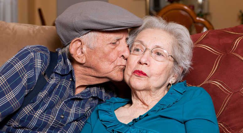 Elderly senior couple in an affectionate pose in a home setting.