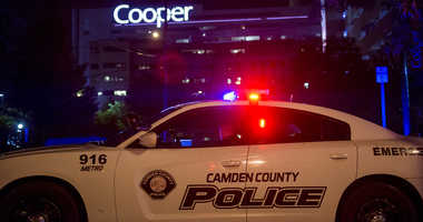An officer is posted by Copper hospital following a shooting that left two detectives wounded in Camden, N.J., Tuesday, Aug. 7, 2018.