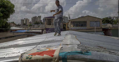 Jorge Ortiz works to tie down his roof as he prepares for the arrival of Tropical Storm Dorian, in the Martín Peña neighborhood of San Juan, Puerto Rico, Tuesday, Aug. 27, 2019. The construction worker was taking no chances as Dorian approaches.