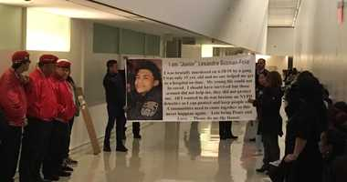 Supporters carry a Justice For Junior banner into Bronx Criminal Court.