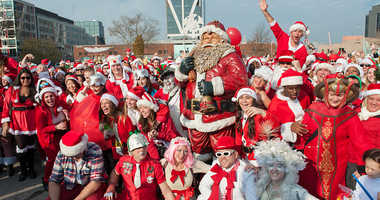 A crowd of people dressed as Santa gather for a group photo during the annual SantaCon pub crawl