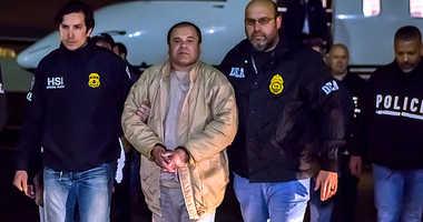El Chapo is escorted by DEA agents.