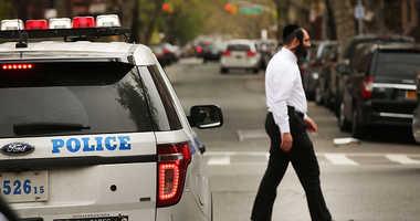 A Hasidic man walks by a police car in a Jewish Orthodox neighborhood in Brooklyn