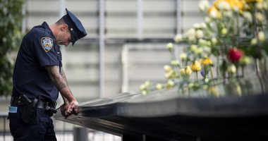 A New York City Police Department (NYPD) officer pauses while visiting the North pool during a commemoration ceremony for the victims of the September 11 terrorist attacks at the National September 11 Memorial,
