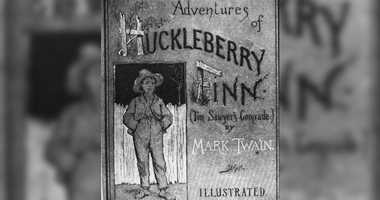 Cover of the book 'Adventures of Huckleberry Finn (Tom Sawyer's Comrade)' by Mark Twain (Samuel Clemens), 1884. The illustration, by E. M. Kimble, shows a young boy who stands in front of a picket fence while wearing a straw hat.