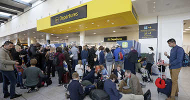 People wait outside the departures gate at Gatwick airport, near London, as the airport remains closed with incoming flights delayed or diverted