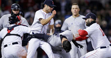 Boston Red Sox relief pitcher Joe Kelly, left, throws a punch at New York Yankees' Tyler Austin, center, as they fight during the seventh inning of a baseball game at Fenway Park in Boston, Wednesday, April 11, 2018. (AP Photo/Charles Krupa)