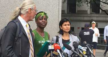 Patricia Oukoumo with attorney Ron Kuby outside of court.