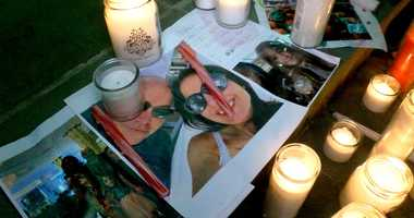 Photos of Keith Caneiro, his wife Jennifer, and children Jesse and Sophia are shown under candles during a vigil held outside the Colts Neck Town Hall.