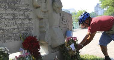Pham Van Khanh, a 62-year-old retiree, lays flowers at the monument of Senator John McCain in Hanoi, Vietnam, Monday, Aug. 27, 2018.
