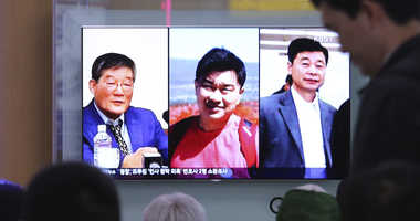 In this May 3, 2018 photo, people watch a TV news report screen showing portraits of three Americans, Kim Dong Chul, left, Tony Kim and Kim Hak Song, right, detained in the North Korea