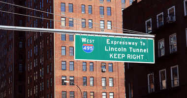 Street sign for West 495 Expressway to Lincoln Tunnel hangs above road in New York City