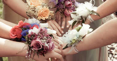 Girls showing off their flower wrist corsages before the prom