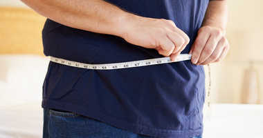 Close Up Of Overweight Man Measuring Waist
