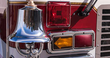 Bright chrome and brass bell on the front of a fire truck and front lights.