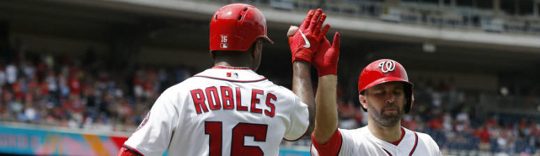 Brian Dozier high fives Victor Robles after hitting a home run.