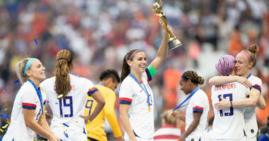 The USWNT celebrates with the World Cup trophy.