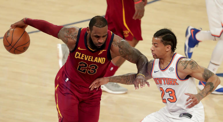 Cleveland Cavaliers forward LeBron James, left, drives against New York Knicks guard Trey Burke, right, during the third quarter of an NBA basketball game, Monday, April 9, 2018, in New York. (AP Photo/Julie Jacobson)