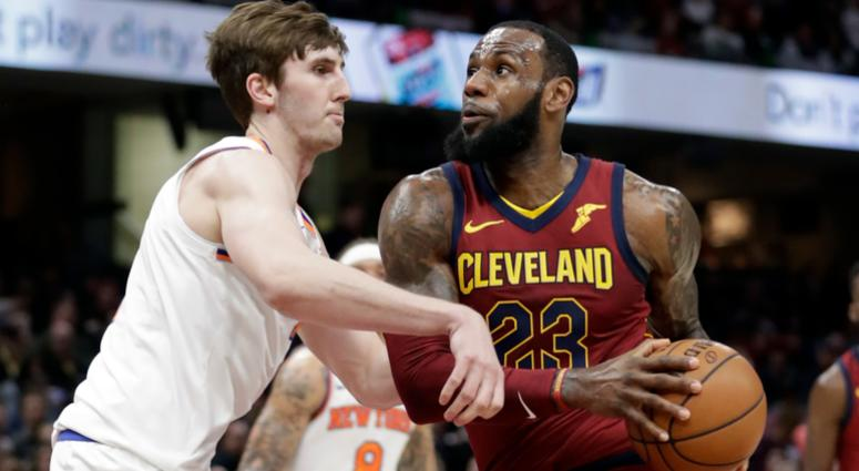 Cleveland Cavaliers' LeBron James, right, drivers past New York Knicks' Luke Kornet, from Switzerland, in the first half of an NBA basketball game, Wednesday, April 11, 2018, in Cleveland.