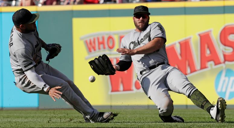 Chicago White Sox's Daniel Palka, right, cannot catch a ball hit by Cleveland Indians' Edwin Encarnacion in the fifth inning of a baseball game, Monday, May 28, 2018, in Cleveland. Yoan Moncada, left, watches. Encanacion was safe at second base for a doub