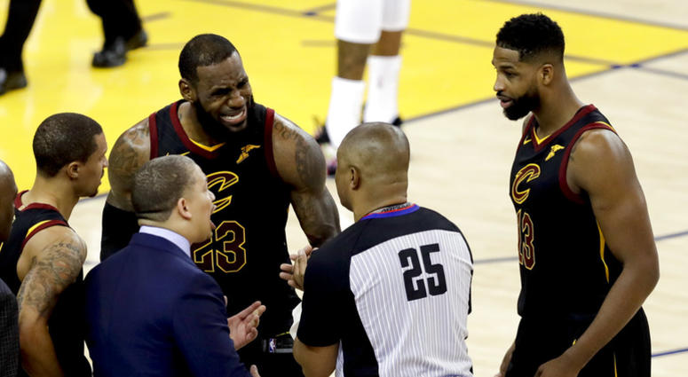 Cleveland Cavaliers forward LeBron James (23) and head coach Tyronn Lue, bottom, talk with referee Tony Brothers (25) during the second half of Game 1 of basketball's NBA Finals against the Golden State Warriors in Oakland, Calif., Thursday, May 31, 2018.