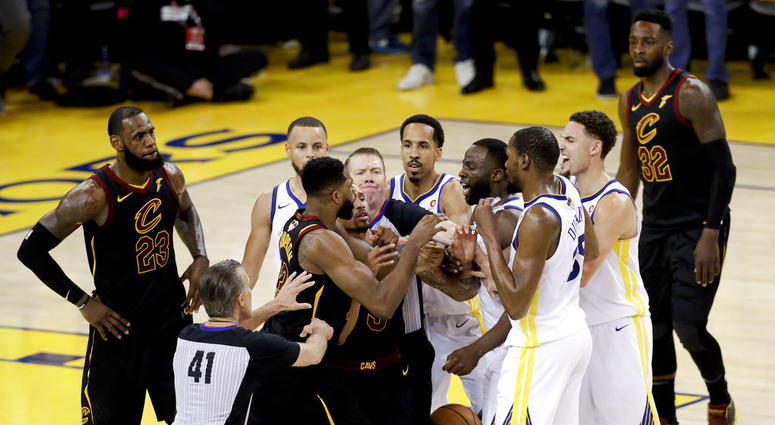 An official tries to separate Cleveland Cavaliers center Tristan Thompson and Golden State Warriors forward Draymond Green during overtime of Game 1 of basketball's NBA Finals in Oakland, Calif., Thursday, May 31, 2018. The Warriors won 124-114.