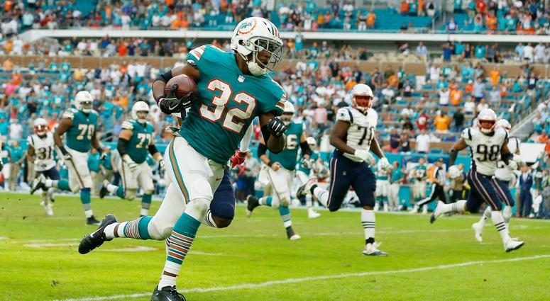 MIAMI, FL - DECEMBER 09: Kenyan Drake #32 of the Miami Dolphins carries the ball for the game winning touchdown defeating the New England Patriots 34-33 at Hard Rock Stadium on December 9, 2018 in Miami, Florida. (Photo by Michael Reaves/Getty Images)