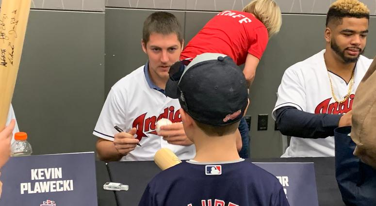 Trevor Bauer hands an autographed baseball to a young fan
