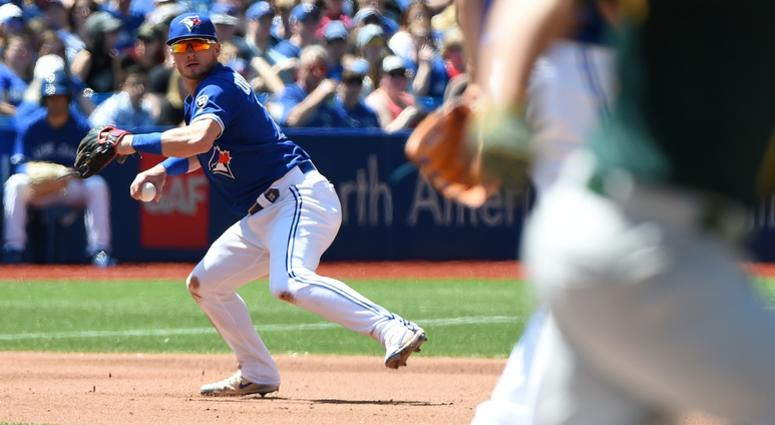 Toronto Blue Jays third baseman Josh Donaldson (20) fields a ball but cannot make the throw on an infield single by Oakland Athletics catcher Jonathan Lucroy (21) in the fifth inning at Rogers Centre.
