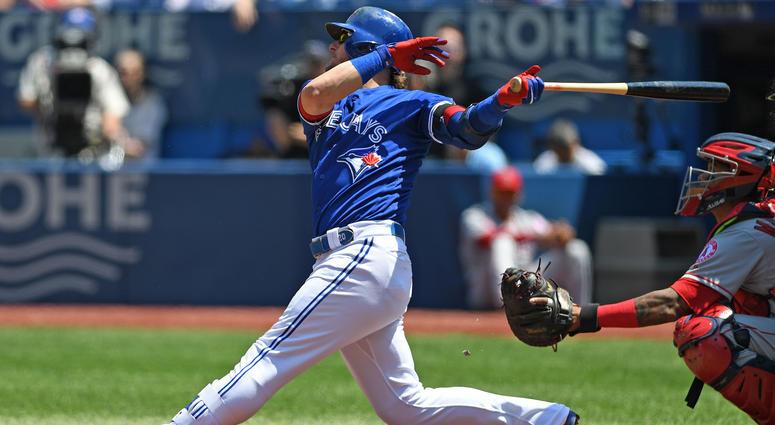 May 24, 2018; Toronto, Ontario, CAN; Toronto Blue Jays third base Josh Donaldson (20) hits a single during the regular season MLB game between the Los Angeles Angels and Toronto Blue Jays at Rogers Centre.