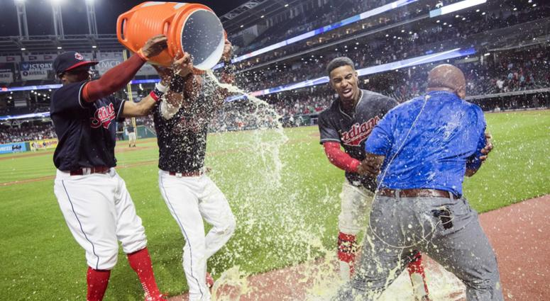 Aug 8, 2018; Cleveland, OH, USA; Cleveland Indians center fielder Rajai Davis (26) and catcher Yan Gomes (7) douse shortstop Francisco Lindor (12) and television personality Andre Knott with Gatorade after Lindor ended the game with a three-run home run a