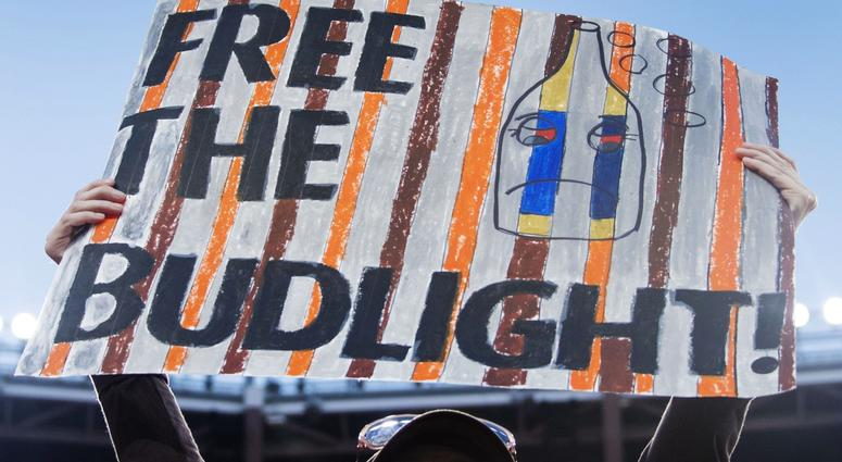 Janelle Clemons holds a sign referencing the free beer that will be given away by Budweiser if the Cleveland Browns win a game at FirstEnergy Stadium.