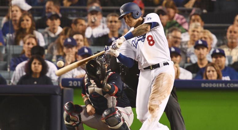 Oct 27, 2018; Los Angeles, CA, USA; Los Angeles Dodgers shortstop Manny Machado (8) hits a single against the Boston Red Sox in the eighth inning in game four of the 2018 World Series at Dodger Stadium. Mandatory Credit: Robert Hanashiro-USA TODAY Sports