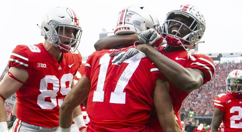Ohio State Buckeyes wide receiver Chris Olave (17) is congratulated by tight end Luke Farrell (89) and wide receiver Binjimen Victor (9) after scoring a touchdown against the Michigan Wolverines at Ohio Stadium.