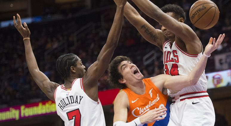 Dec 23, 2018; Cleveland, OH, USA; Cleveland Cavaliers forward Cedi Osman (16) drives to the basket between Chicago Bulls forward Justin Holiday (7) and forward Wendell Carter Jr. (34) at Quicken Loans Arena. Mandatory Credit: Ken Blaze-USA TODAY Sports