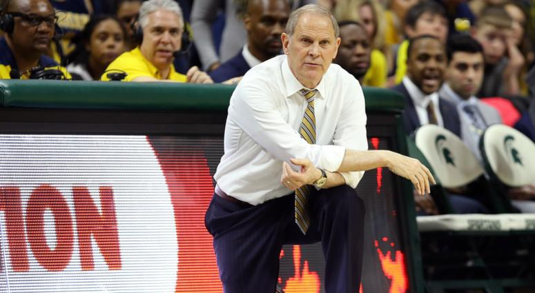 Michigan Wolverines head coach John Beilein knees on the court during the second half of a game against the Michigan State Spartans at the Breslin Center.