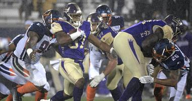 Atlanta Legends running back Lawrence Pittman rushes in front of Orlando Apollos defensive end Anthony Moten Jr. during the second half of an Alliance of American Football game Saturday, Feb. 9, 2019 in Orlando, Florida.
