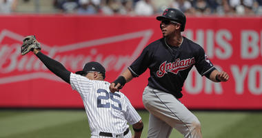 New York Yankees second baseman Gleyber Torres (25) holds up the ball as Cleveland Indians' Michael Brantley looks for the call on a force out at second base during the fourth inning of a baseball game, Saturday, May 5, 2018, in New York. Brantley was out