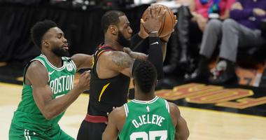 Boston Celtics' Semi Ojeleye (37) and Boston Celtics' Jaylen Brown, left, double-team Cleveland Cavaliers' LeBron James, center, in the second half of Game 3 of the NBA basketball Eastern Conference finals