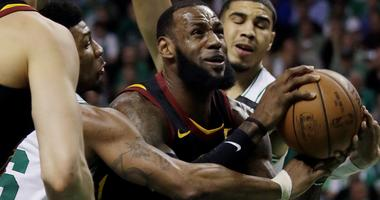Cleveland Cavaliers forward LeBron James drives against Boston Celtics guard Marcus Smart, left, and forward Jayson Tatum, right, during the first quarter of Game 5 of the NBA basketball Eastern Conference finals