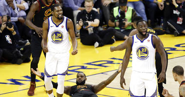 Cleveland Cavaliers forward LeBron James (23) reacts between guard Jordan Clarkson (8) and Golden State Warriors forward Kevin Durant during the second half of Game 1 of basketball's NBA Finals in Oakland, Calif., Thursday, May 31, 2018.
