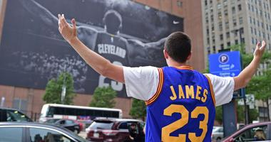 In this June 9, 2017, file photo, Cleveland Cavaliers fan Jordan Phillips poses for a photo in front of a poster featuring Cleveland Cavaliers forward LeBron James, before Game 4 of the basketball's NBA Finals between the Cavaliers and Golden State