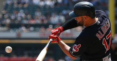 Cleveland Indians' Yonder Alonso hits an RBI single against the Chicago White Sox during the first inning of a baseball game Sunday, Aug. 12, 2018, in Chicago.