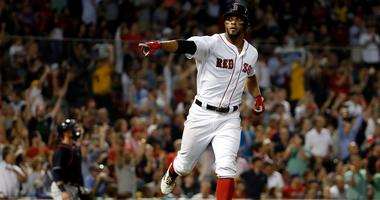 Boston Red Sox's Xander Bogaerts points to teammates in the dugout after his home run against the Cleveland Indians during the fourth inning of a baseball game Wednesday, Aug. 22, 2018, in Boston.