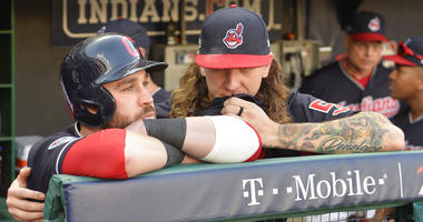 Cleveland Indians' Jason Kipnis, left, is hugged by starting pitcher Mike Clevinger after the Houston Astros defeated the Indians 11-3 in Game 3 of a baseball American League Division Series, Monday, Oct. 8, 2018, in Cleveland. (AP Photo/Phil Long)