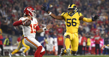 Kansas City Chiefs quarterback Patrick Mahomes, left, passes under pressure from Los Angeles Rams defensive end Dante Fowler (56) during the first half of an NFL football game Monday, Nov. 19, 2018, in Los Angeles. (AP Photo/Kelvin Kuo)