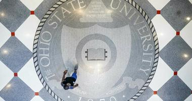 """FILE - In this May 18, 2019 file photo, pedestrians pass through Ohio State University's student union in Columbus, Ohio. Ohio State University wants to trademark the word """"The"""" when used as part of the school's name on university merchandise. The school"""