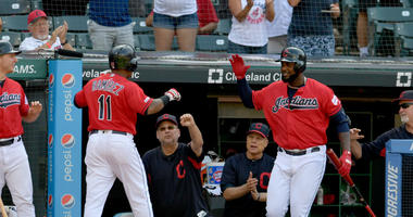 CLEVELAND, OHIO - AUGUST 07: Jose Ramirez #11 celebrates with Terry Francona #77 and Franmil Reyes #32 of the Cleveland Indians after Ramirez hit a solo homer during the second inning of game two of a double header against the against the Texas Rangers at